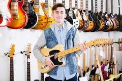 Adolescente masculino que examina las guitarras eléctricas Imagenes de archivo