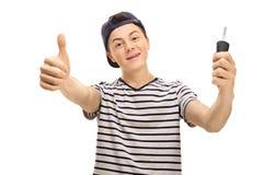 Adolescente masculino que hace el pulgar encima del gesto y que lleva a cabo llave del coche Imagen de archivo