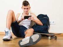 Adolescente masculino que juega con el teléfono Imágenes de archivo libres de regalías
