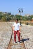 Adolescente masculino que se coloca en un parque y gafas de sol que llevan en sudor Foto de archivo libre de regalías