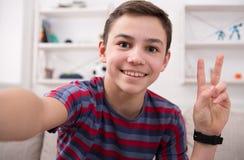 Adolescente masculino que toma el selfie en el teléfono en casa Foto de archivo libre de regalías