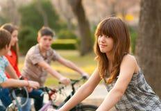 Adolescente mignonne avec ses amis sur des bicyclettes Photos stock