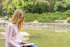 Adolescente mignonne lisant un livre en parc de ville Photographie stock