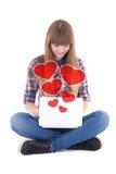 Adolescente mignonne reposant et envoyant des messages d'amour avec l'ordinateur portable Images stock