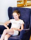Adolescente mignonne s'asseyant dans le fauteuil photos libres de droits