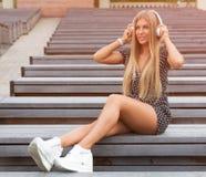 Adolescente milenario feliz moderno con los auriculares, sonriendo, al aire libre en parque en día de verano soleado Foto de archivo