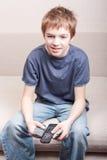 Adolescente mira la televisión y sostiene el telecontrol tres Imagen de archivo