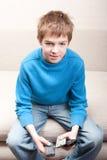 Adolescente mira la televisión y sostiene el telecontrol tres Fotografía de archivo