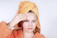 Adolescente mirando en trapo del espejo la cara con el cojín de algodón Foto de archivo