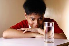 Adolescente mirando un vidrio de agua en una tabla de madera Imagen de archivo libre de regalías
