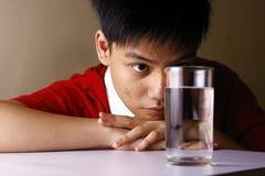 Adolescente mirando un vidrio de agua en una tabla de madera Fotografía de archivo libre de regalías