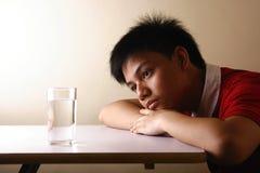 Adolescente mirando un vidrio de agua en una tabla de madera Imagenes de archivo