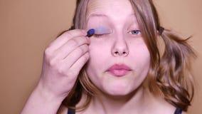 Adolescente modelo da beleza que olha a câmera e que aplica o maleup em sua cara, 4K UHD filme