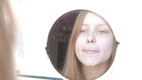 Adolescente modelo de la belleza que mira en el espejo y que aplica el lápiz labial 4K almacen de metraje de vídeo