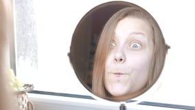 Adolescente modelo de la belleza que mira en el espejo y que hace caras divertidas 4K almacen de video