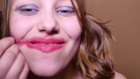 Adolescente modelo de la belleza que mira la cámara y que aplica el maleup en su cara, 4K UHD almacen de video