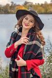 Adolescente modelo que presenta en el lago en una capa roja y un sombrero negro Imágenes de archivo libres de regalías