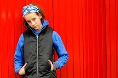 Adolescente moderno contra la pared roja Imagen de archivo