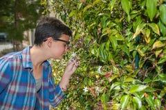 Adolescente moderno en las gafas de sol que paran para oler las flores Imagenes de archivo