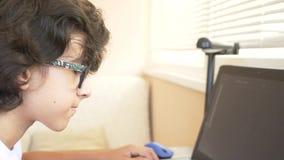 Adolescente moderno hermoso del muchacho que trabaja en una tableta gr?fica ?l mira la pantalla del ordenador port?til 4k, c?mara almacen de metraje de vídeo