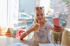 Adolescente moderno que sonríe mientras que hace el selfie Fotografía de archivo