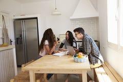 Adolescente montrant le smartphone à ses amis dans une cuisine Image libre de droits