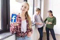 Adolescente montrant le smartphone avec le logo de facebook avec des amis derrière Photos stock