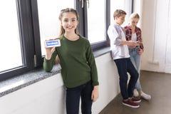 Adolescente montrant le smartphone avec le logo de facebook avec des amis derrière Images libres de droits