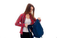 Adolescente moreno bastante joven de los estudiantes en ropa elegante y la mochila en su presentación de las manos aisladas en el Fotografía de archivo libre de regalías