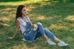 Adolescente moreno delgado en los guardapolvos de los vaqueros que mienten en la hierba en el parque Fotos de archivo libres de regalías