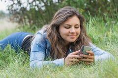 Adolescente moreno fresco que ve su teléfono elegante al aire libre Imágenes de archivo libres de regalías
