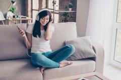 Adolescente moreno hermoso emocionado está escuchando la música en whi grande Fotos de archivo libres de regalías