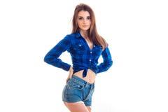 Adolescente moreno hermoso en una camisa de tela escocesa y un dril de algodón pone en cortocircuito la presentación para la cáma Imágenes de archivo libres de regalías