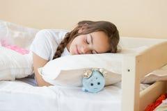 Adolescente moreno hermoso que duerme en el despertador la píldora Imagen de archivo