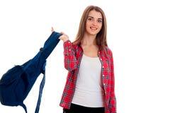Adolescente moreno joven hermoso de los estudiantes en ropa elegante y la mochila en la presentación de las manos aisladas en el  Foto de archivo