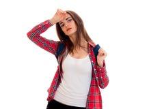 Adolescente moreno joven hermoso de los estudiantes en ropa elegante y la mochila en su presentación de los hombros aisladas en b Imágenes de archivo libres de regalías