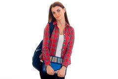 Adolescente moreno joven lindo de los estudiantes en ropa elegante y la mochila en su presentación de los hombros aisladas en bla Imagenes de archivo