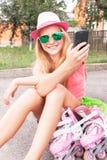 Adolescente (muchacha) con los zapatos del patinaje sobre ruedas usando el teléfono elegante Foto de archivo libre de regalías