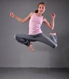 Adolescente muscular joven sano que salta y que baila en estudio Niño que ejercita con el salto en fondo gris Foto de archivo
