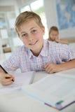 Adolescente na escrita da sala de aula no caderno Foto de Stock