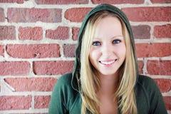 Adolescente na frente da parede de tijolo fotografia de stock royalty free