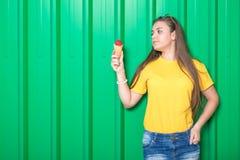 Adolescente na moda com gelado no fundo verde da parede fotos de stock royalty free