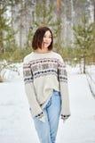 Adolescente na queda de neve da floresta do inverno foto de stock