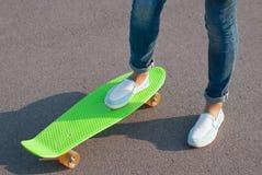 Adolescente nas calças de brim com um skate Foto de Stock Royalty Free