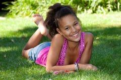 Adolescente negro joven que miente en la hierba Imágenes de archivo libres de regalías