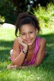 Adolescente negro joven que miente en la hierba Fotografía de archivo libre de regalías