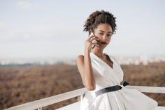 Adolescente negro que habla en smarthpone en balcón de gran altura Foto de archivo libre de regalías