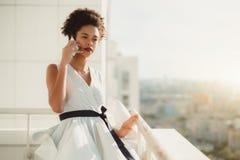 Adolescente negro que habla en smarthpone en balcón del rascacielos Imagen de archivo libre de regalías