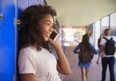 Adolescente negro que usa smartphone en el tiempo de la rotura en escuela Imágenes de archivo libres de regalías