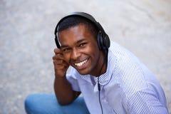 Adolescente negro sonriente con los auriculares Foto de archivo